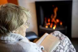 homebournd_senior_woman_reading_fireplace